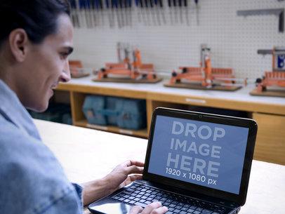 Mockup of Engineer at Industrial Workshop Using an HP Laptop