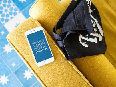 Silver iPhone 8 Plus Mockup Lying on a Yellow Sofa Near a Bag a21506