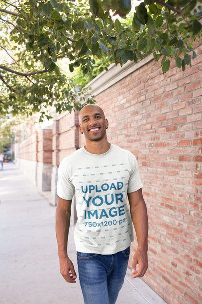 T-Shirt Mockup Featuring a Happy Man Walking Under a Tree 18234