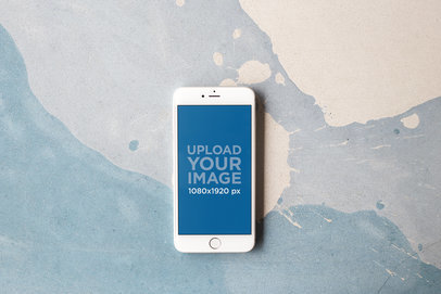 Silver iPhone Mockup Featuring a Cream Paint Stain on a Soft Blue Surface a21616
