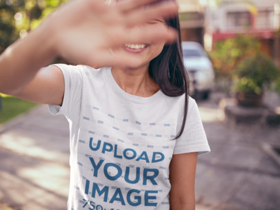 T-Shirt Mockup of a Happy Girl Blocking the Camera with her Hand 20567