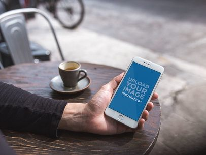 Mockup of an iPhone 8 Plus Being Held at a Coffee Shop 21607