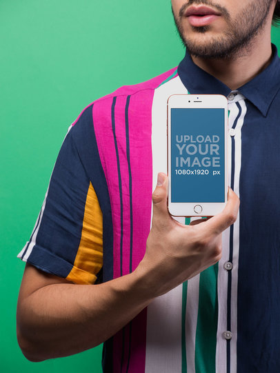 Mockup of a Man Showing an iPhone 8 Plus Wearing a Colorful Shirt Against a Green Wall 21740