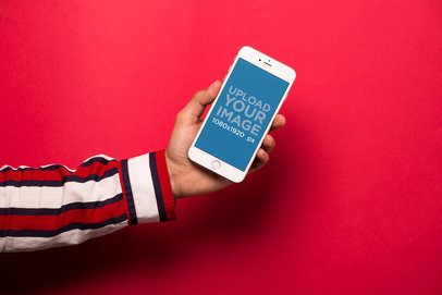 Mockup of an iPhone Held Against a Red Wall 21743