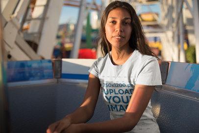 Mockup of a Girl Wearing a T-Shirt Sitting on a Ferris Wheel Cabin 18326