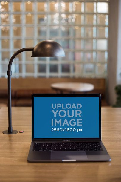 MacBook Mockup on a Wooden Table Next to a Lamp 21623