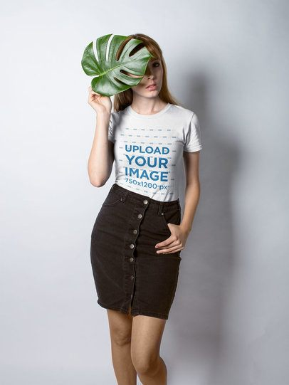 Mockup of a Fashionable Girl Wearing a T-Shirt Holding a Leaf Against her Face 18363