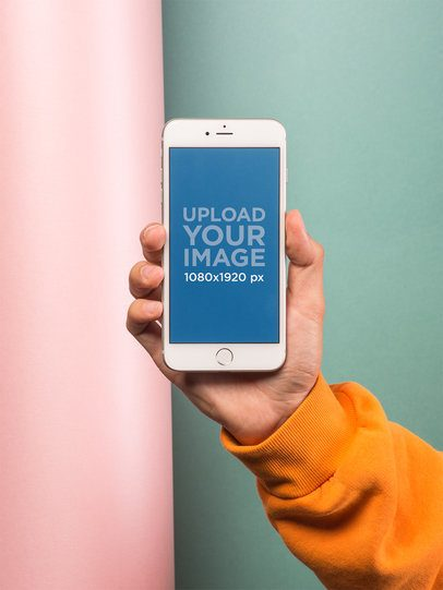 Mockup of a Hand Holding a Silver iPhone In Front of a Colorful Wall 21769