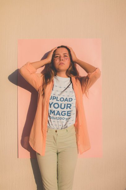 Crew-Neck Tee Mockup Featuring a Girl Wearing a Light Orange Shirt Posing Against a Salmon Color Cardboard 18418