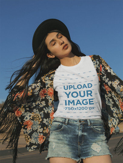 T-Shirt Mockup of a Woman Closing Her Eyes and Holding Her Fedora 18886