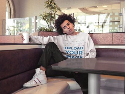 Sweatshirt Mockup of a Guy with Afro Hair Posing Inside a Restaurant Holding a Soda 18330