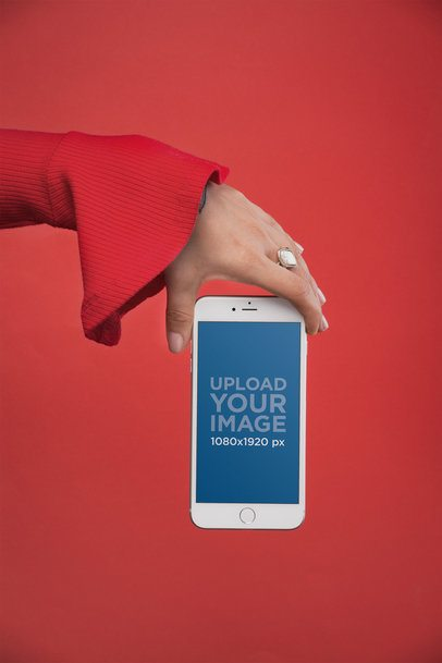 Mockup of a Woman's Hand with a White Ring Showing an iPhone 8 Plus Against a Red Background 21980