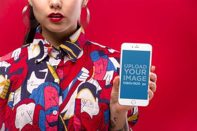 Mockup of a Woman with Hoop Earrings Wearing a Colorful Shirt Showing a Silver iPhone 8 Against a Red Background 21961
