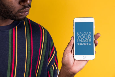 Mockup of a Man with a Holding an iPhone Against a Yellow Wall 22129