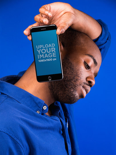 Mockup of a Man Holding a Space Gray iPhone 8 Against a Vivid Blue Background 22088