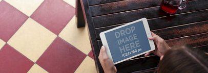 Tablet Mockup of a Woman Using an iPad Mini at a Restaurant