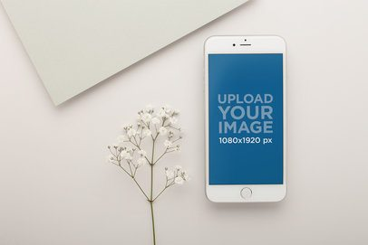 Silver iPhone Mockup Lying Next to Small White Flowers 22019