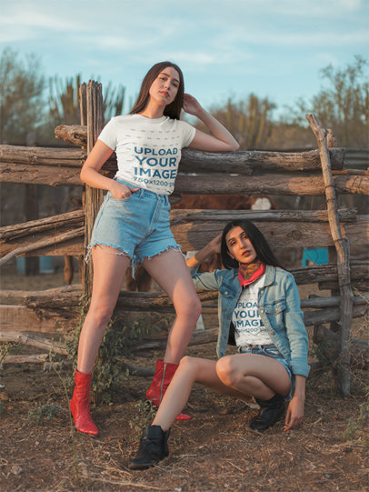 Round Neck Tee Mockup of Two Young Models Wearing a Stylish Country Outfit Against a Wooden Fence 18865