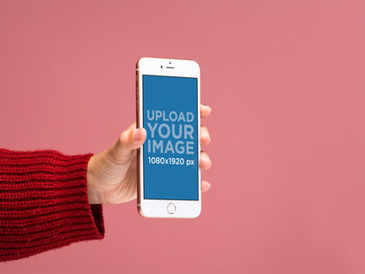 Mockup of a Gold iPhone 8 Plus in front of a Salmon Colored Background 22162