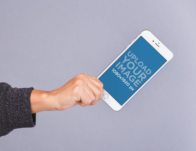 Mockup of a Hand Holding an iPhone 8 Plus in an Angled Position Against a Gray Surface 22167