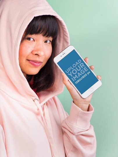 Mockup of a Girl Showing an iPhone 8 Plus Wearing a Pink Hoodie 22171