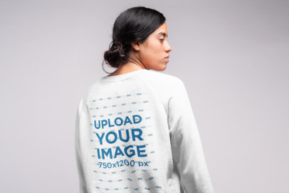 Back View Sweatshirt Mockup of a  Serious Girl with a Messy Hair Bun 21546