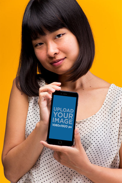Mockup of an iPhone 8 Plus Held by a Woman Wearing a Polka Dot Shirt 22174