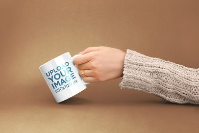 Mockup of a Female Hand Holding a Coffee Mug Against a Flat Color 22372