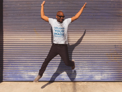 T-Shirt Mockup of a Happy Man Jumping in Front of a Garage 20778