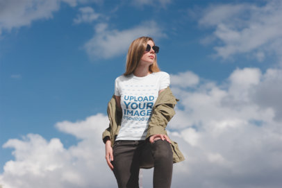 T-Shirt Mockup Featuring a Stylish Woman Posing Against a Blue Sky  19456