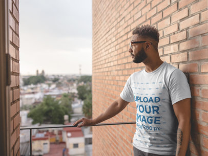 T Shirt Mockup Featuring a Handsome Man Standing in a Balcony 21334