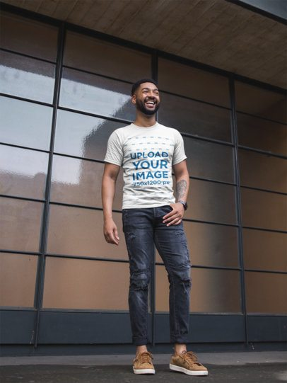 T-Shirt Mockup of a Stylish Man Smiling in Front of a  Window Wall 21348