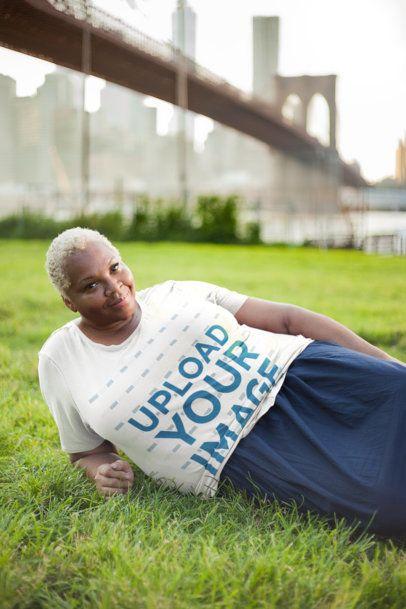 Mockup of a Woman Wearing a Plus Size T-Shirt Laying on Grass 22567