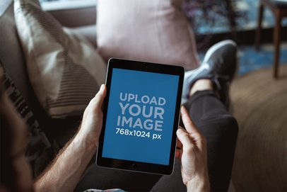 Mockup of an iPad Being Used by a Man While Resting on a Couch 22611
