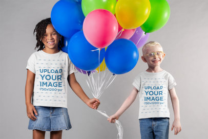 Mockup of Two Kids Wearing T-Shirts and Holding Party Balloons Together 22045