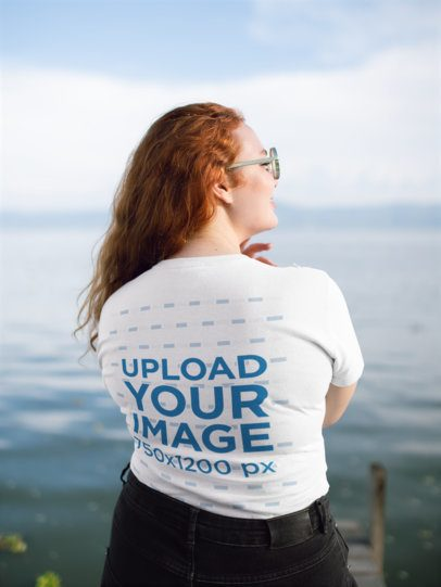 Back View T-Shirt Mockup of a Red-Haired Woman Facing a Lake 21938