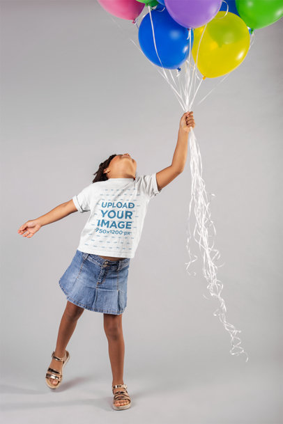 Mockup of a Little Girl Wearing a T-Shirt Holding Balloons in a Studio 22051