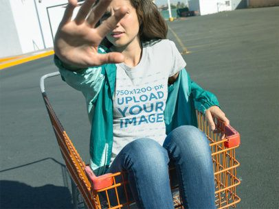 T-Shirt Mockup of a Woman in a Shopping Cart Blocking the Camera from Her Face 18480