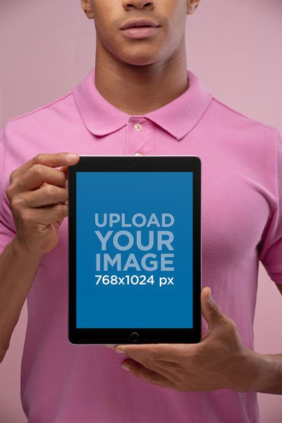 Mockup of a Man Holding an iPad Wearing a Pink Polo Shirt 22630