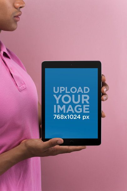 Mockup of a Man Holding a Space Gray iPad in a Pink Environment 22631