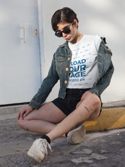 Mockup of a Tattooed Short-Haired Girl Wearing a T-Shirt Sitting at a Parking Lot 18285