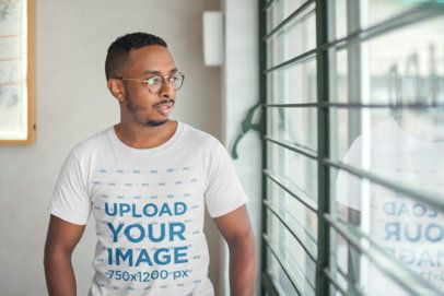 Round Neck Tee Mockup of a Man with Glasses Facing a Window 21039
