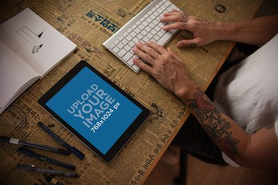 Mockup of an iPad in Portrait Position Lying on a Table Next to a Tattooed Man Using a Keyboard 22832
