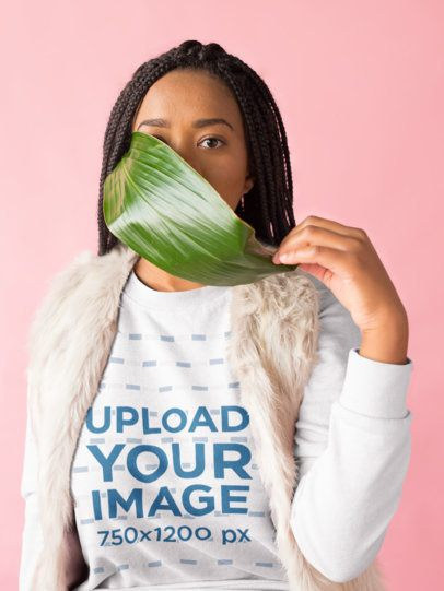 Mockup of a Girl with Braids Wearing a Sweater Holding a Big Leaf Against her Mouth 18374