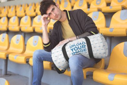 Mockup of a Man Holding a Duffel Bag on a Stadium Seat 23249