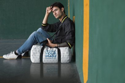 Mockup of a Man Sitting Against a Wall with a Duffel Bag 23241