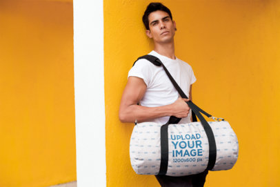 Duffle Bag Mockup of a Man Leaning Against a Yellow Wall 23224