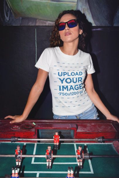 Mockup of a Girl Wearing a T-Shirt Leaning Over a Foosball Table 22282