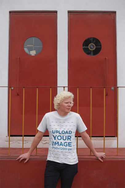 T-Shirt Mockup of a Man Standing in Front of Two Red Doors 22241
