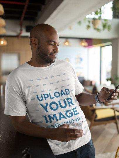 Tshirt Mockup of a Man Using His Phone at a Restaurant 21703